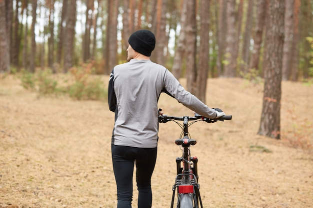 Back view of professional cyclist choosing path in forest, looking aside, holding sport bicycle, united with nature, being fond of sport, leading healthy lifestyle.