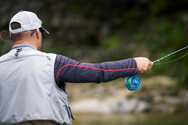 Back view of professional fisherman in special uniform using spinning for fishing in mountain river. concept of sport hobby on fresh air.