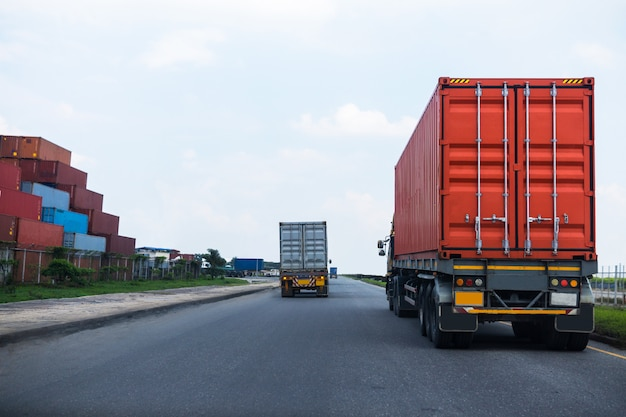 Back view of red container truck in ship port logistics