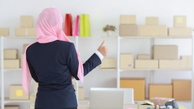 파란색 양복을 입고 머리에 분홍색 샤프트를 얹은 종교적인 아시아 이슬람 여성이 자신감을 갖고 고개를 들고 있습니다. 비즈니스 우먼은 패키지 sme 상자 배달 배경으로 서 있습니다. 집에서 일하기 개념