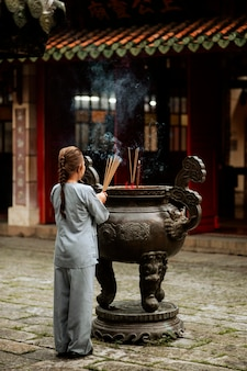 Back view of religious woman with burning incense at the temple