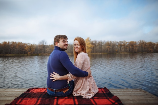 Back view of romantic young couple sitting on pier and hugging on background with amazing view