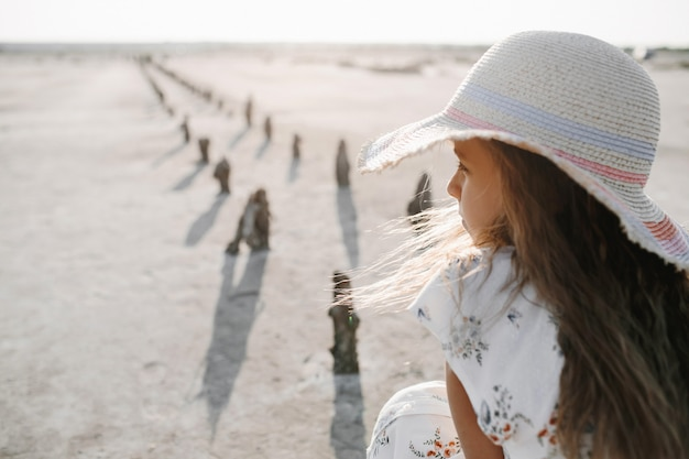 Back view of sad little girl on the sand beach on the sunny day dressed in hat