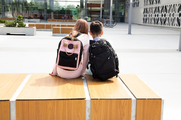 Back view of school students with backpacks sitting on bench in schoolyard