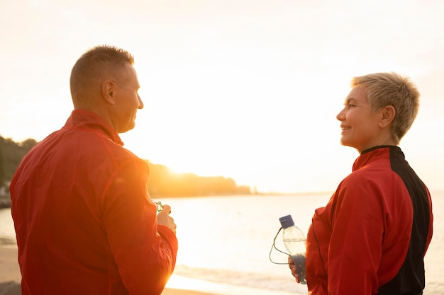 Back view of senior couple on the beach during jogging