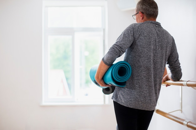 Back view senior man holding yoga mat