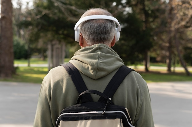 Back view senior man listening to music in a headset