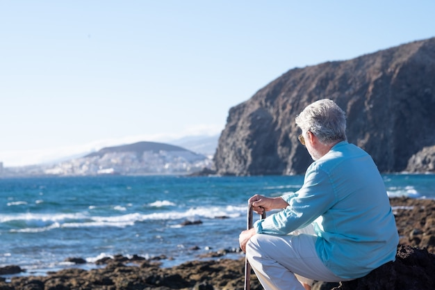 Back view of senior man sitting at sunset light on the beach holding a walking stick because of body aches, looking at horizon over water