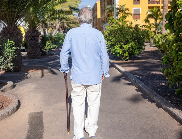 Back view of senior man with a stick walking outdoors in sunny day