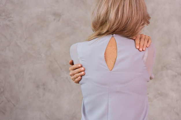 Back view senior woman holding herself