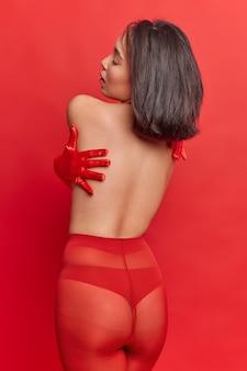 Vista posteriore della donna sessuale con i capelli scuri indossa collant e guanti ha culo sexy senza cellulite si abbraccia in pose contro il muro rosso vivo ha un corpo perfetto