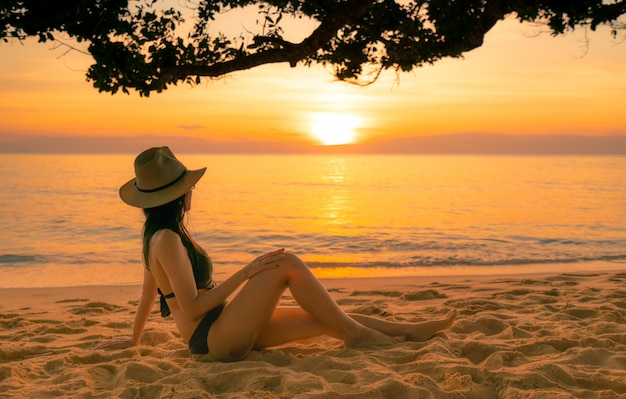 Back view of sexy woman sit on sand and watching sunset at tropical beach