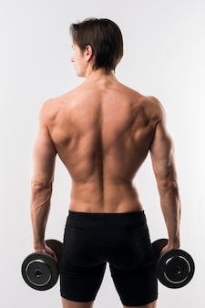Back view of shirtless athletic man holding weights