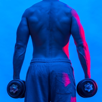 Back view of shirtless fit man holding weights