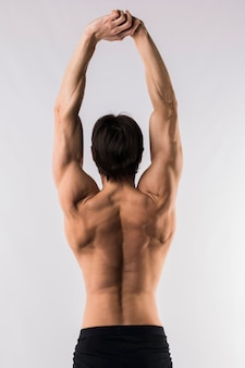 Back view of shirtless muscled man with arms up