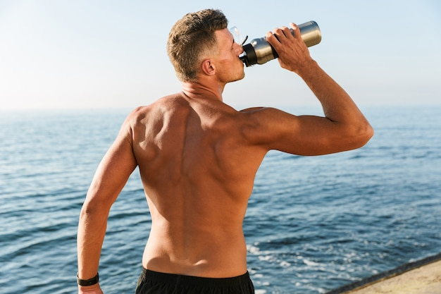 Back view of shirtless sportsman drinking water