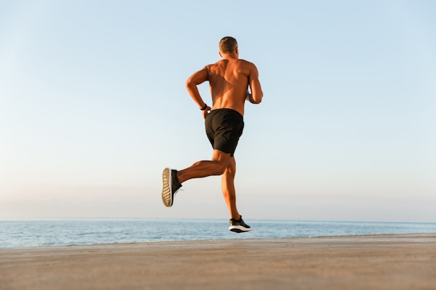 Back view of a shirtless sportsman with earphones running