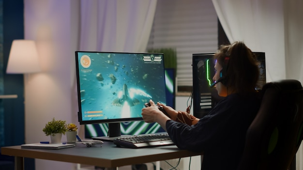 Back view shot of excited woman gamer streaming online video games and wining playing on rgb powerful computer using wireless controller. player with headphones celebrating victory in gaming room
