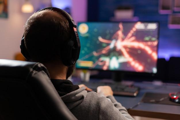 Снимок вид сзади сконцентрированного геймера, транслирующего онлайн-видеоигры на компьютере с помощью беспроводного контроллера. человек-игрок с наушниками играет в игры в комнате с неоновым светом и профессиональным оборудованием