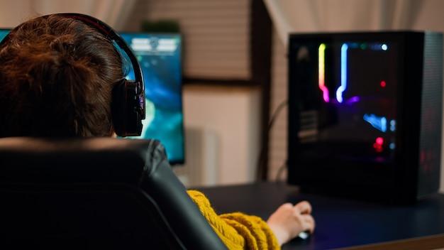 컴퓨터에서 1인칭 슈팅 온라인 비디오 게임을 하는 전문 게이머의 뒷모습. 사이버 공간의 가상 챔피언십, 게임 토너먼트 중 pc에서 수행하는 e스포츠 선수.