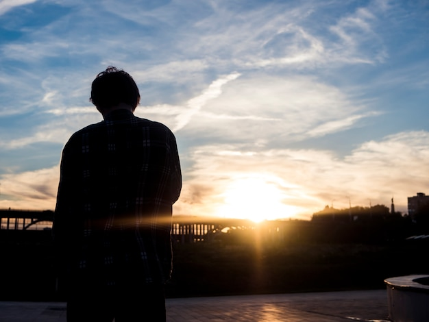 Back view of silhouette of young man standing and looking at the sunset