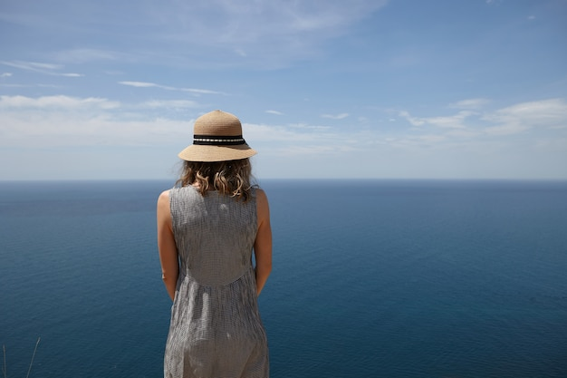 Back view of slim blonde young woman wearing dress and straw hat enjoying sunny weather outdoors, facing vast blue sea, looking into distance. people, nature, seascape, summer and traveling