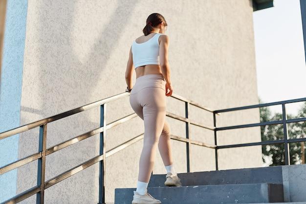 Vista posteriore di una donna magra con una buona forma che indossa abiti sportivi alla moda, leggings beige e top, salendo le scale di allenamento all'aperto, stile di vita sano, allenamento da donna.
