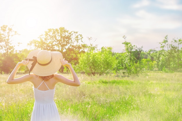 Back view of slim young woman, in fashionable hat, is looking at beautiful nature landscape. romantic girl in white dress is walking and dreaming on spacious field at sunset. provence style.