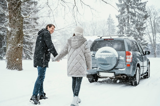 Back view of smiley couple enjoying the snow while on a road trip