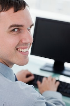 Back view of a smiling businessman using a monitor
