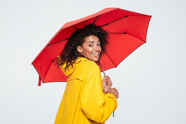 Back view of smiling woman in raincoat hiding under umbrella
