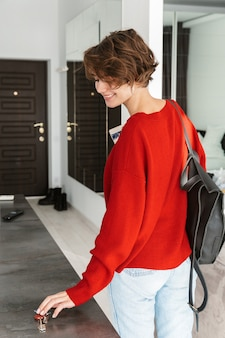 Back view of a smiling woman with backpack leaving her apartment