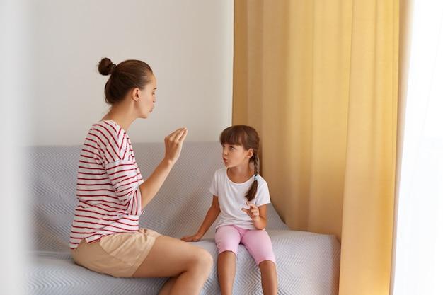 Vista posteriore del logopedista che insegna alla figlia del bambino la pronuncia corretta dei suoni, fisioterapista che lavora su difetti del linguaggio o difficoltà con una bambina piccola al chiuso.