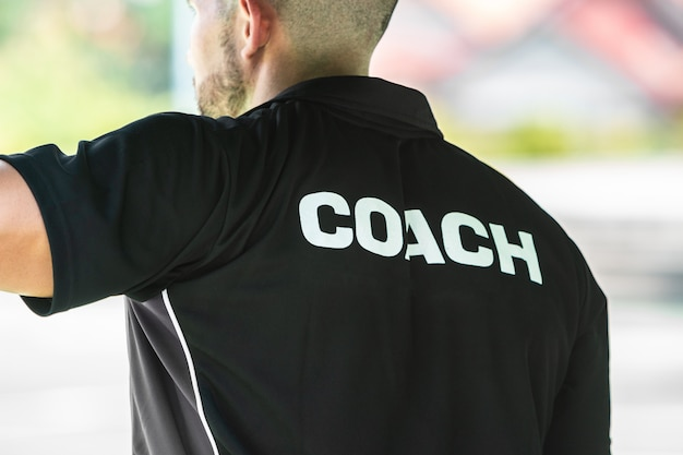 Back view of a sport coach wearing sport shirt with coach word written on it