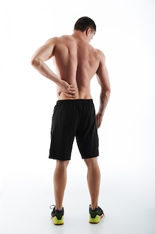 Back view of sportsman have a painful feelings in body.