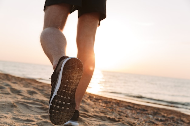 Back view of a sportsmen's legs running on a sand