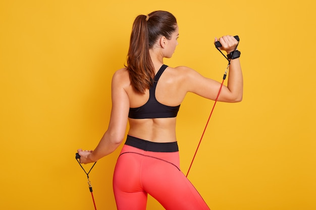 Back view of sporty brunette female stands wearing sporty clothing, working out with expander for back muscles and arms