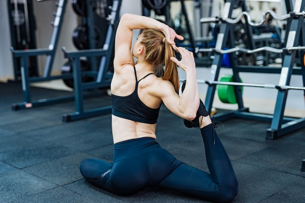 Back view of a sporty trainer in casual top and leggings sitting on the floor in pose while stretching her body in the gym
