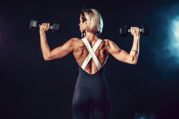 Back view of a sporty woman in fashionable sportswear does the exercises with dumbbells. photo of muscular woman on dark wall with smoke. strength and motivation.