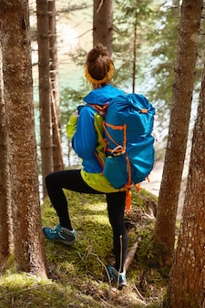 Back view of sporty woman traveler walks on hill through trees, looks down on mountain lake, enjoys being alone in nature