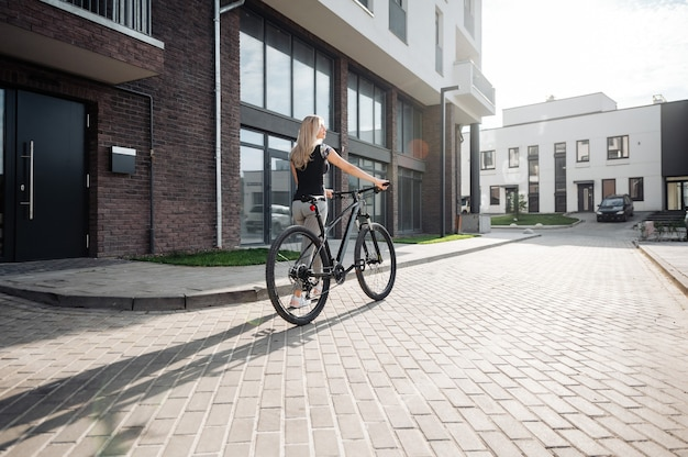 Back view of sporty young woman in active wear walking with black bike at urban area. pleasant lady with blond hair enjoying favorite hobby during sunny days outdoors.