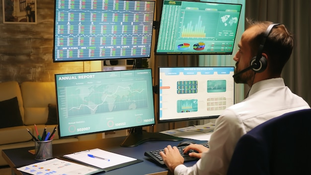 Back view of stock market trader looking at graphs on multiple monitors from home office.