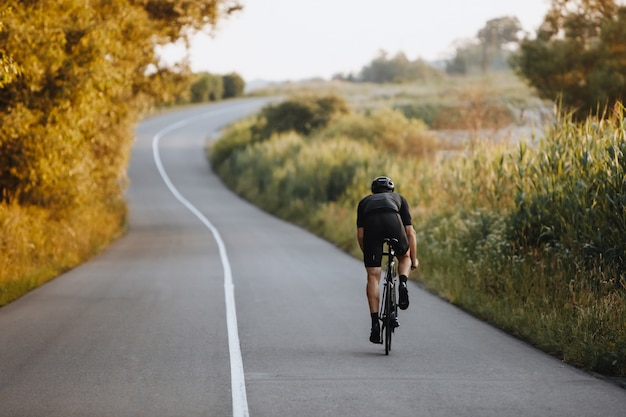 Back view of strong male cyclist with athletic body shape riding bike at the paved road among trees and green bushes