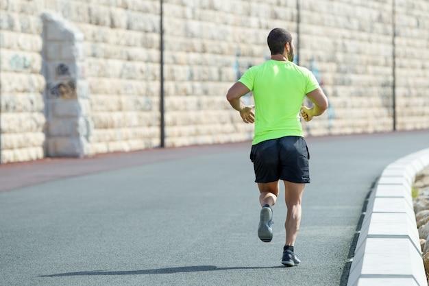 Vista posteriore di uomo sportivo forte che corre sulla strada