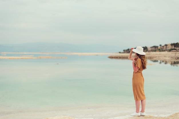 Back view of stylish girl wearing dress on seaside