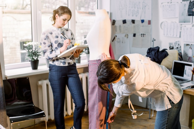 Back view of successful female dressmaker measuring materials on mannequin in atelier office. talented fashion shop owner designer working with sketches for new collection of clothes