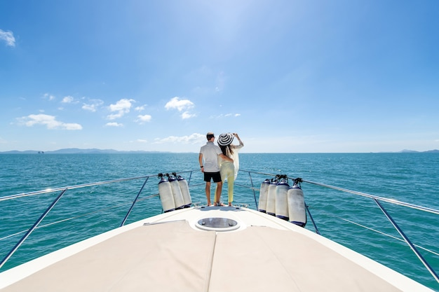 Back view of a sweet couple standing on edge of luxury yacht
