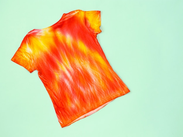 Back view of a t-shirt in tie dye style on a light surface