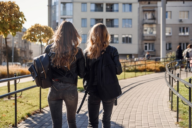 Back view of teen pretty girlfriends with backpacks walking on the street.