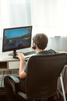 ゲームをしている10代の少年の背面図